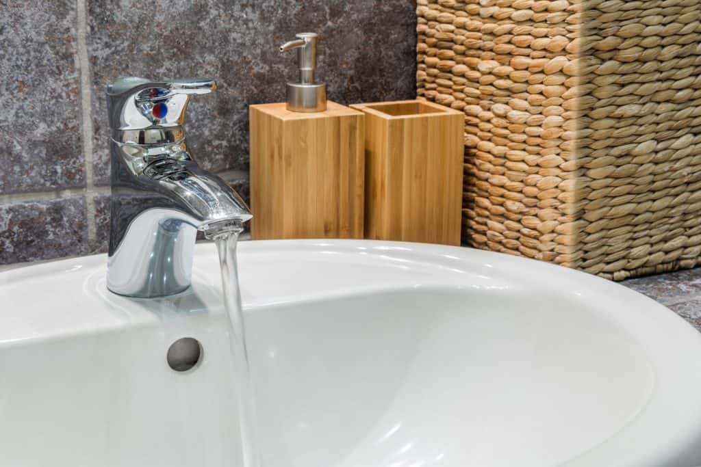 A Japanese inspired bathroom design with a ceramic lavatory and a bamboo hand sanitizer and a wicker bamboo basket