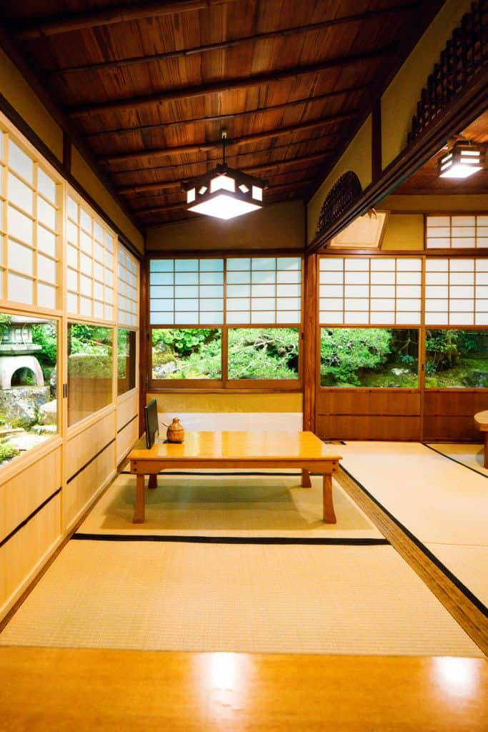 An earthy wooden ceiling and wall living room with tatami mats on the flooring for the dining table