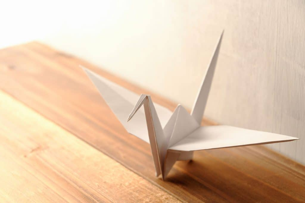 A gorgeously hand made crane origami on a wooden table