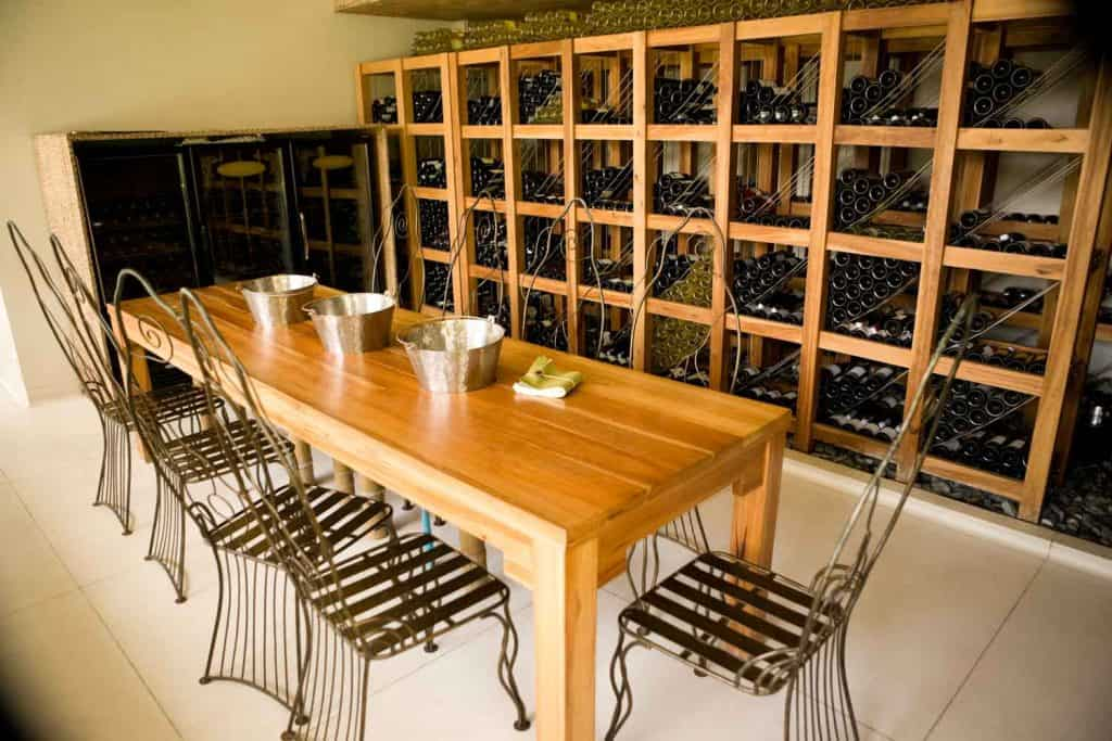 A rustic basement cellar with lots of wine on perfectly arranged wines, a long solid hardwood tables, and metallic chairs on the sides