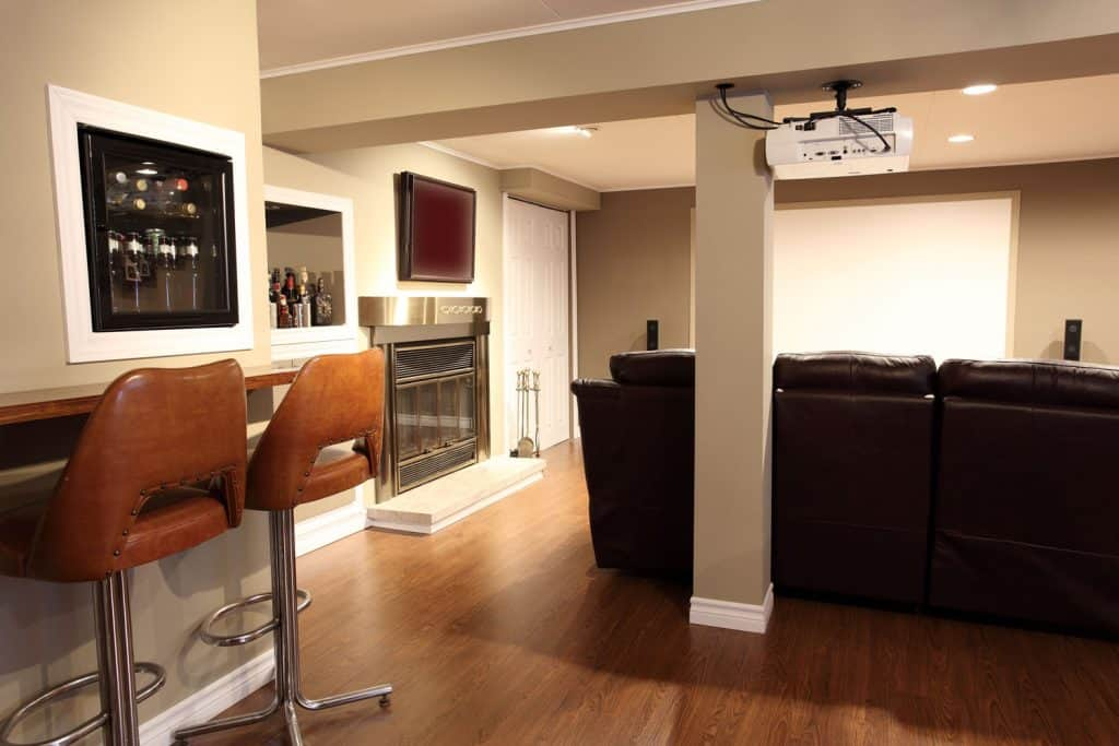 A rustic basement entertainment area with light cream colored walls, laminated wooden flooring, and a dark rustic sofa
