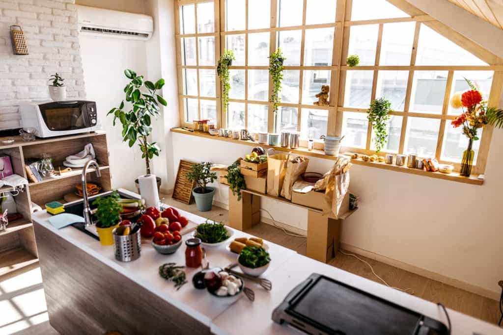 A rustic farmhouse themed dining area with fruits on the breakfast bar, indoor plants on the windows, and grocery bags on a table