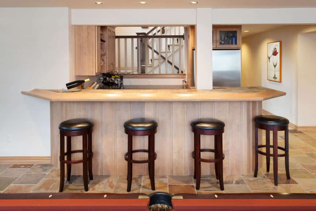 A small bar under a rustic basement with rustic bar stools arranged near the table