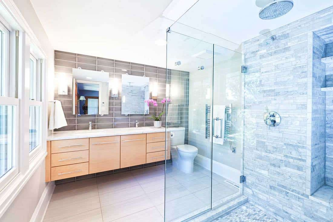 Contemporary home bathroom with glass shower stall and marble tiles