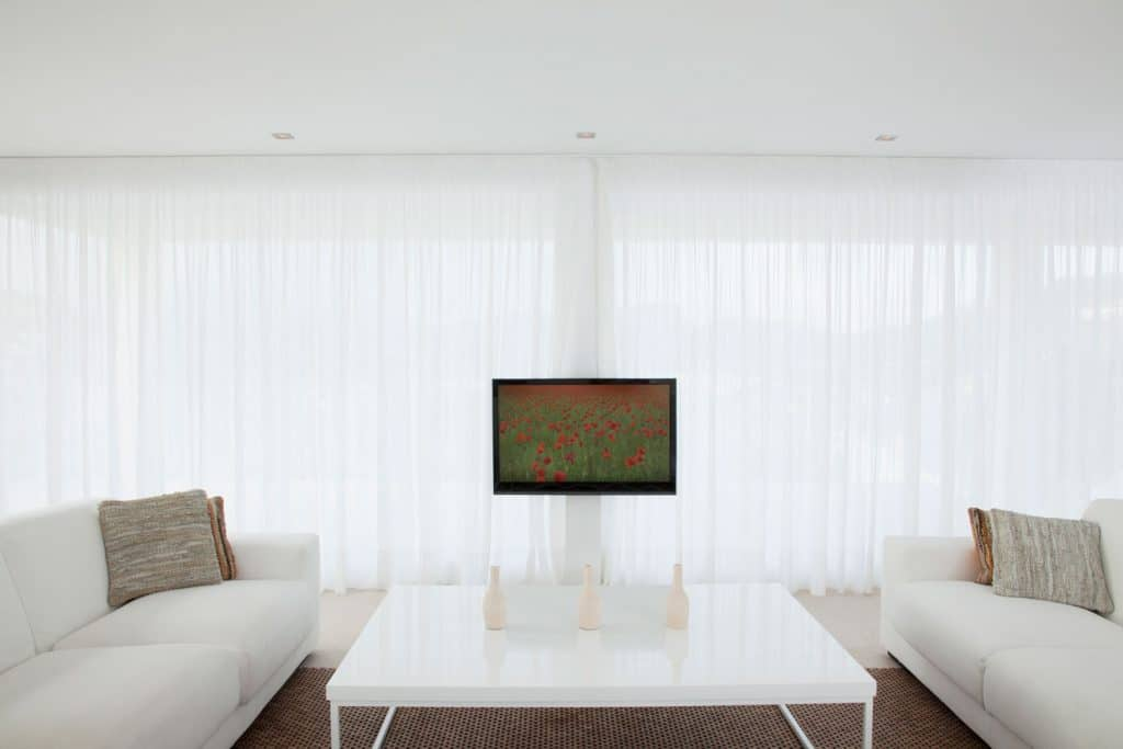 Interior of a contemporary living room with a huge window covered in a long span white curtain