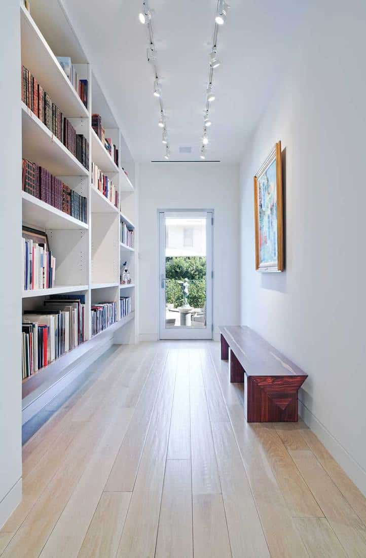 Long hallway with built-in bookcase leading to outdoors