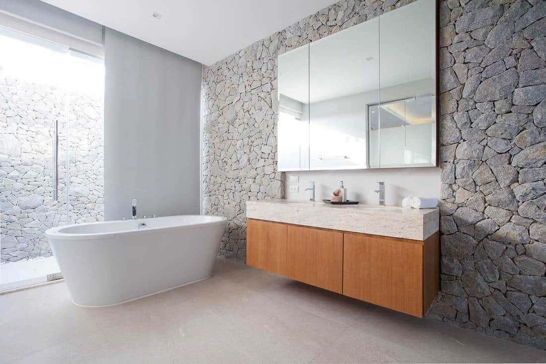 Luxury bathroom features basin and bathtub