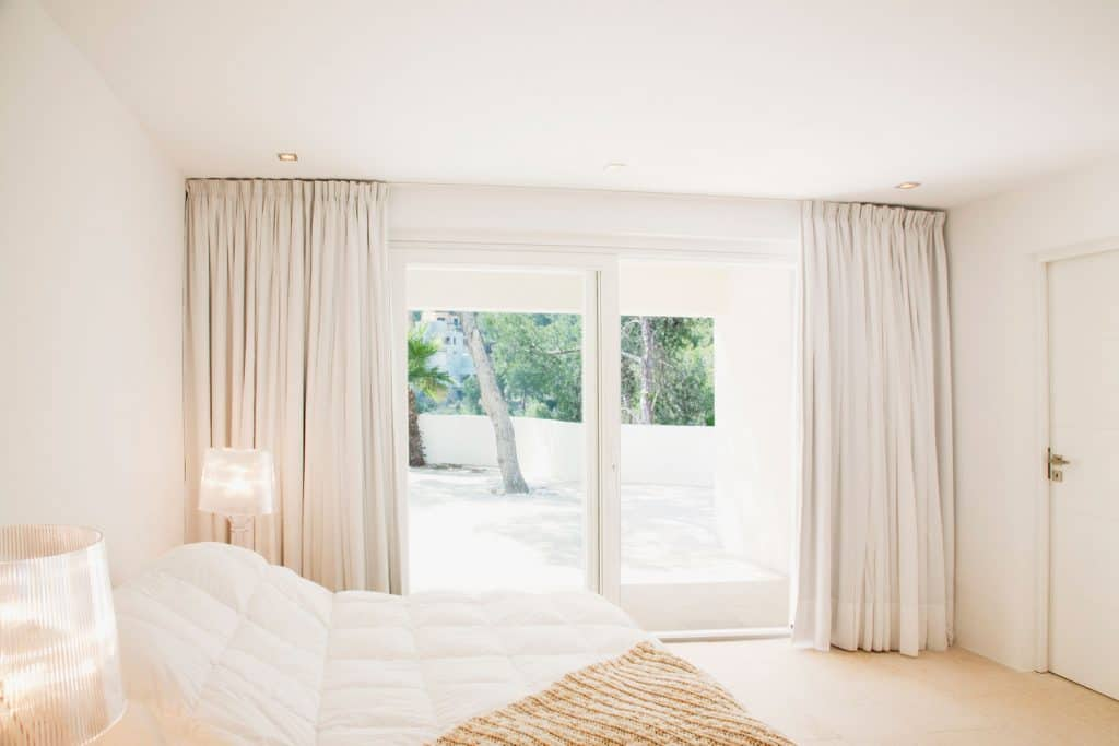 Masters bedroom with white painted walls beige colored curtain cove and an entryway to the patio