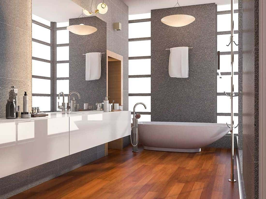Modern bathroom with window and stone tile wall with parquet floor