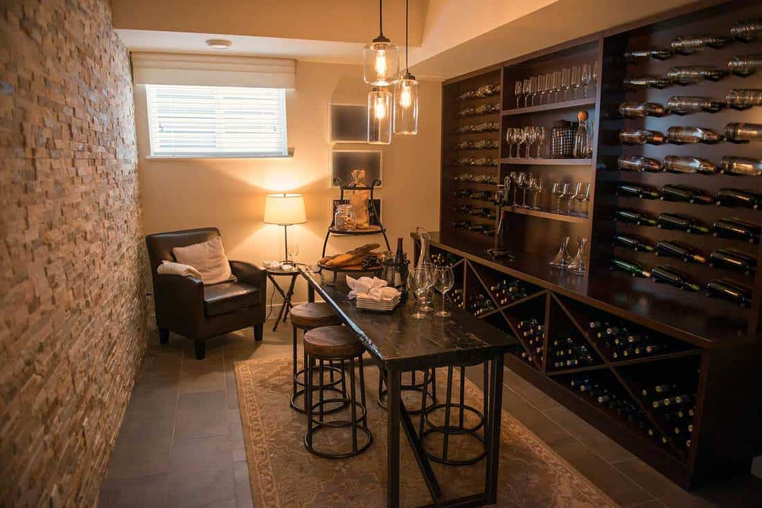 Rustic basement interior with dark dining furniture and wine filled shelves