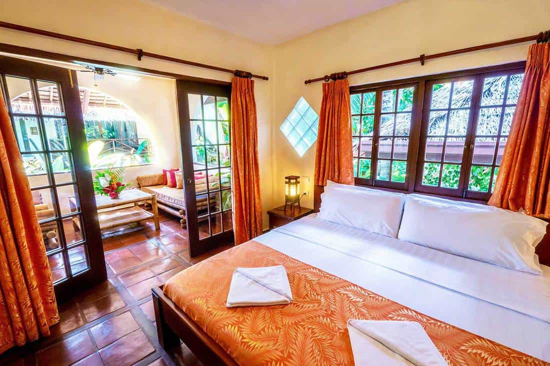 Tropical resort bedroom with yellow walls and wooden french windows and balcony