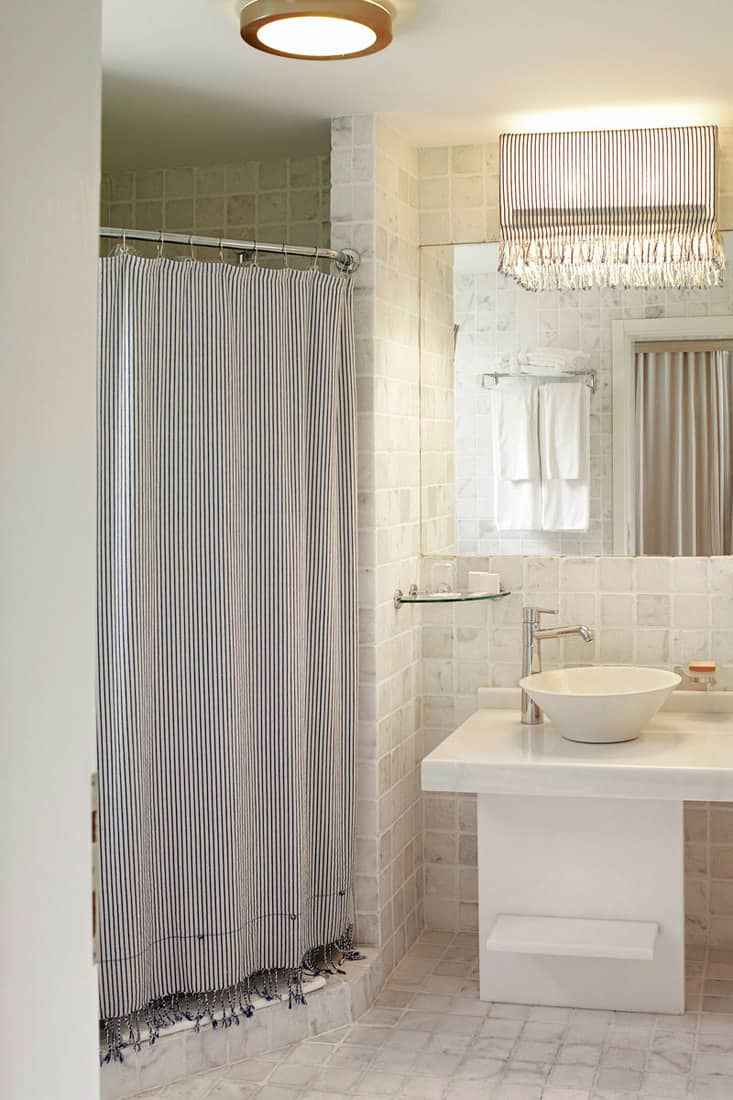 White themed bathroom with stripped gray shower curtain