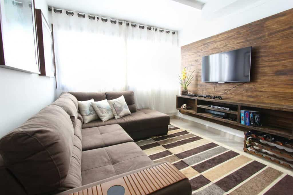Gorgeous modern living room with brown sofa and white colored curtains