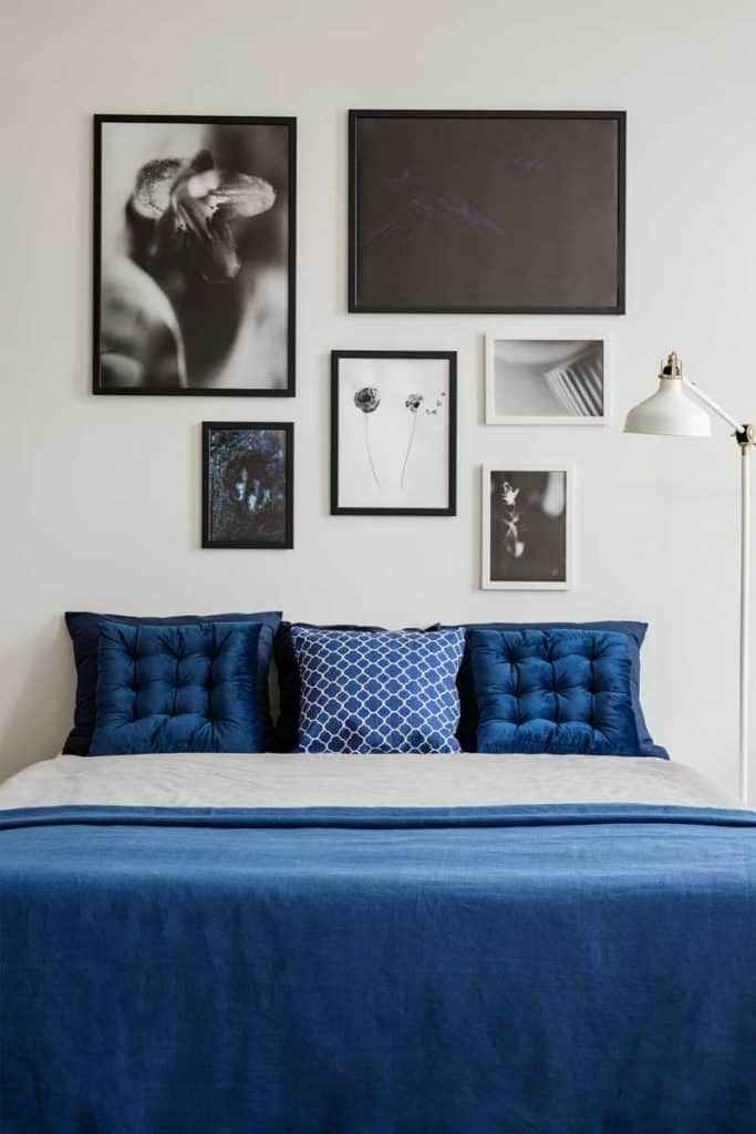Navy blue bedroom with blue pillows and framed wall art decor