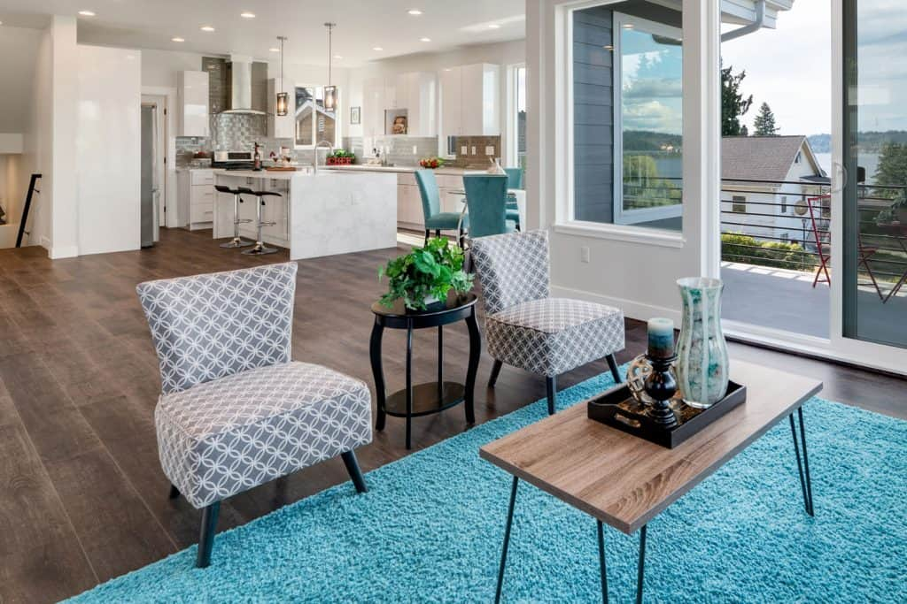 A gorgeous modern living room with wooden laminated flooring, blue colored carpet, and two patterned accent chairs with an end table on the middle