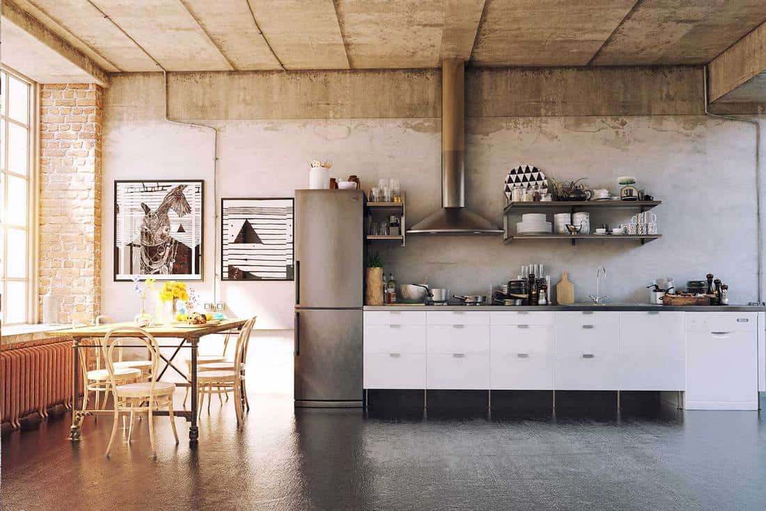 Apartment loft kitchen with dining table, window and abstract paintings