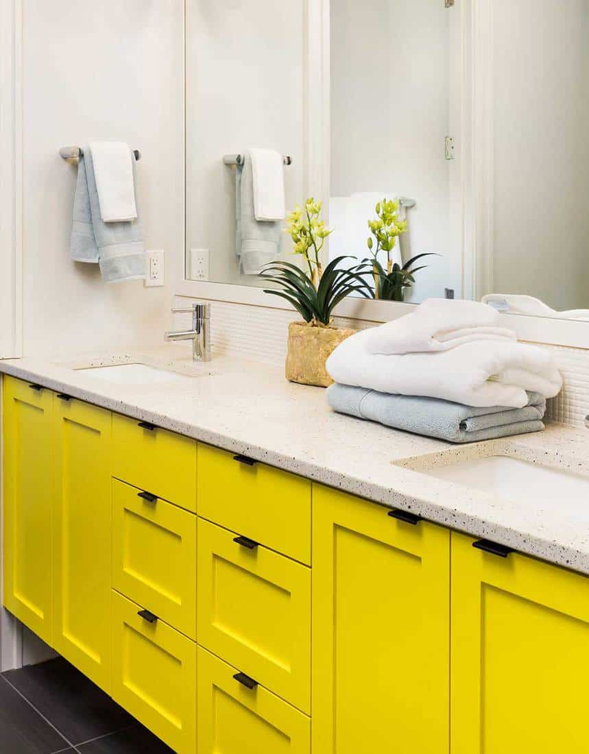 Bathroom sink with white countertop, yellow cabinets, and mirror
