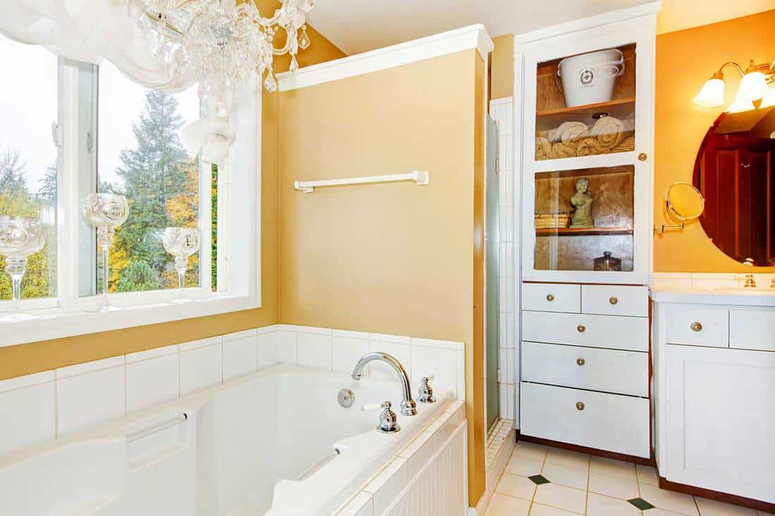 Bathroom with large white tub and storage cabinet
