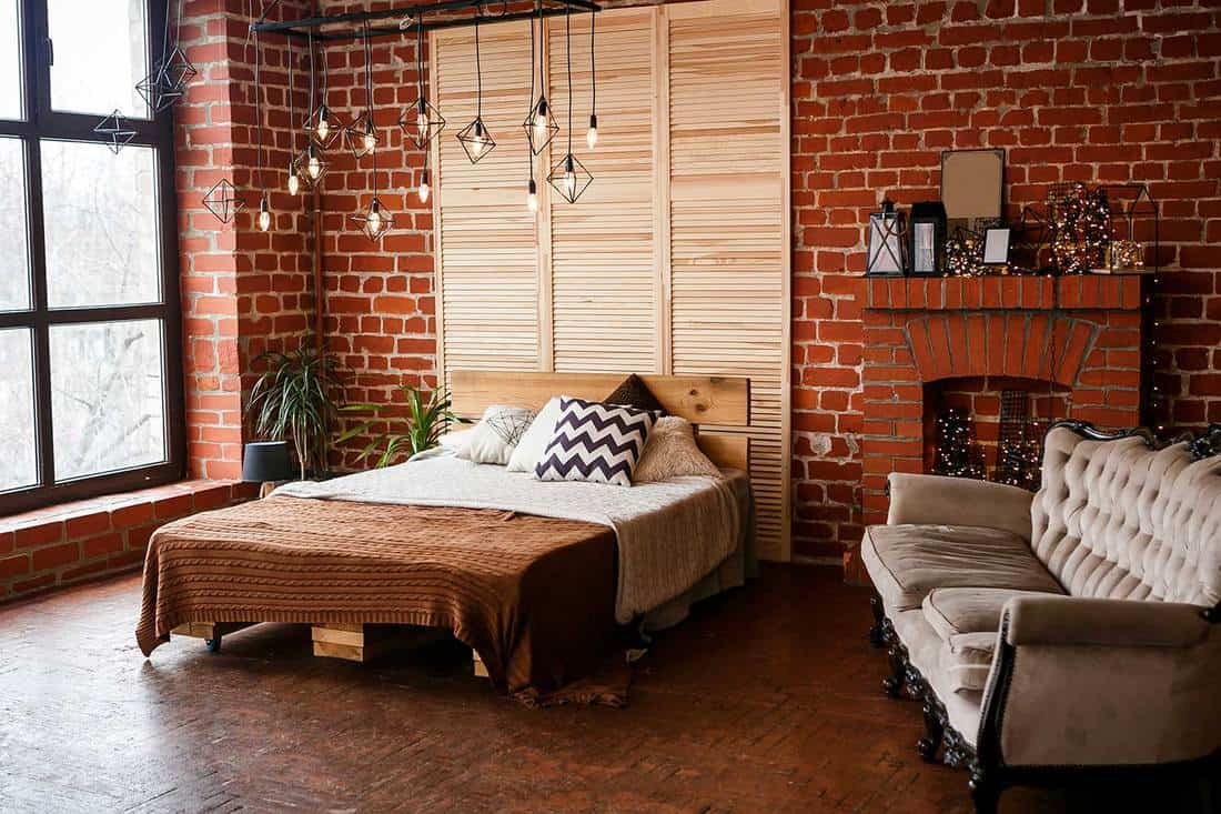 Bedroom with double bed, red brick wall, big window and industrial style interior