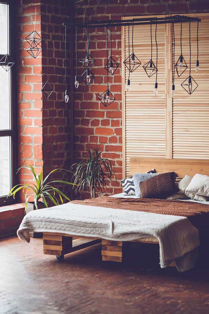 Bedroom with industrial style lighting, big window and double bed