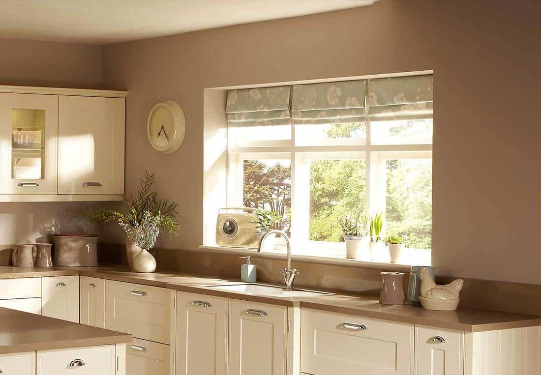 Beige kitchen interior with stylish floral curtain