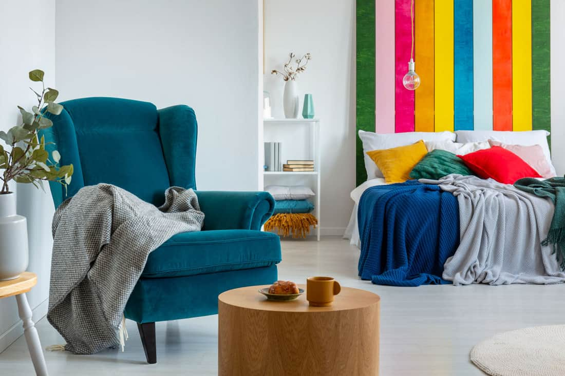 Blue accent chairs with blanket and coffee table in front of it
