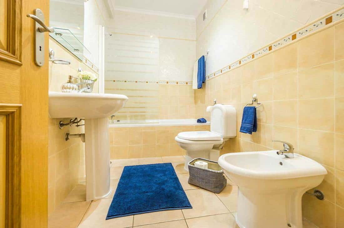 Classic bathroom in warm colors with blue towels and rug