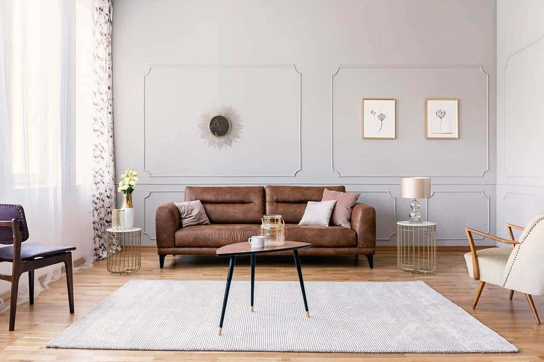 Coffee table with vase and mug in the middle of elegant living room interior