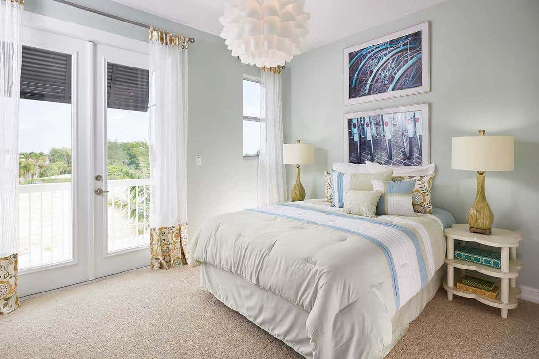 Cozy white bedroom with bicycle painting and beach view windows