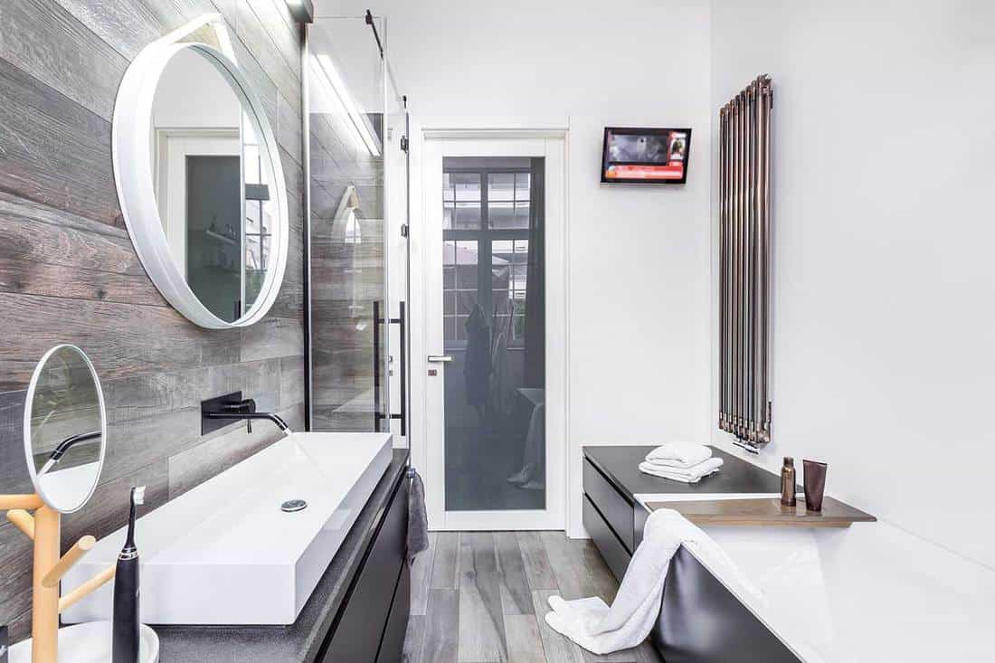 Functional modern bathroom with bathtub, countertop basin, tv and wall heater