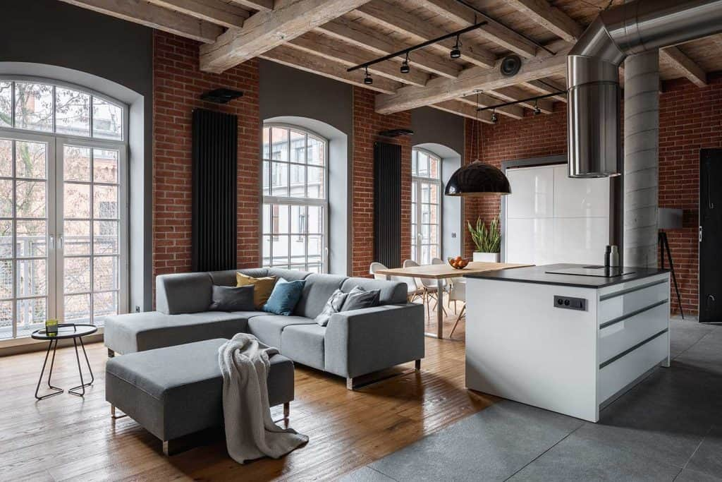 Industrial style loft apartment interior with wooden ceiling, corner sofa and kitchen island