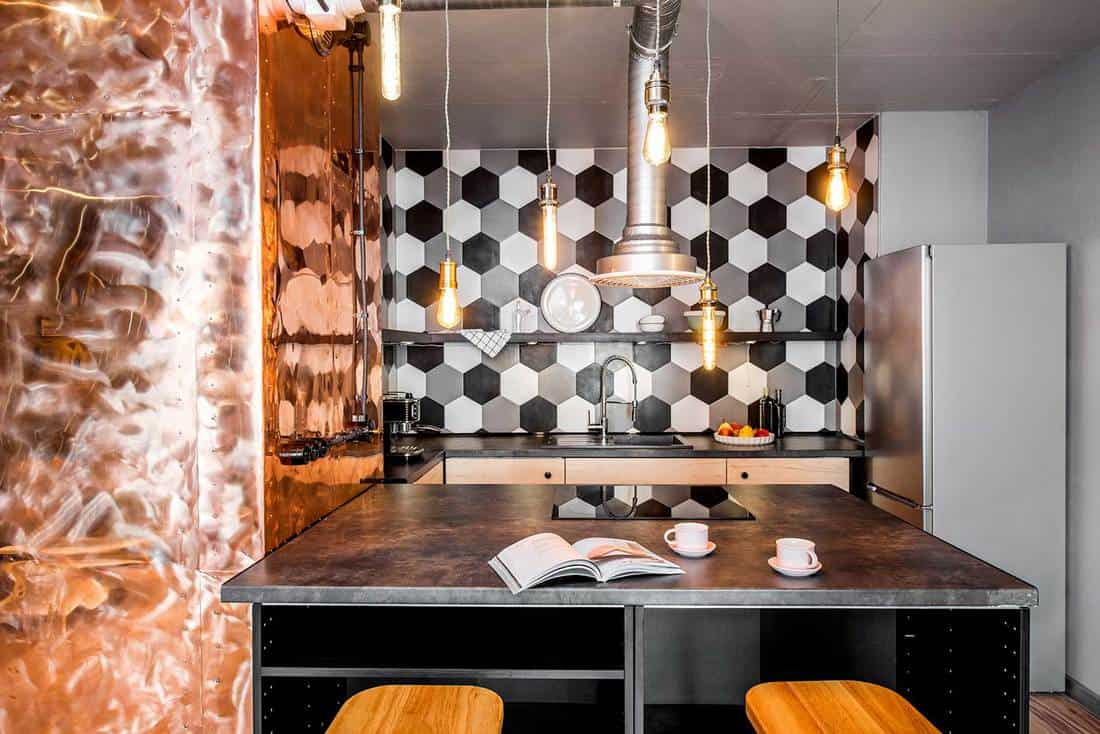 Industrial style loft kitchen with copper wall and hexagonal tiles