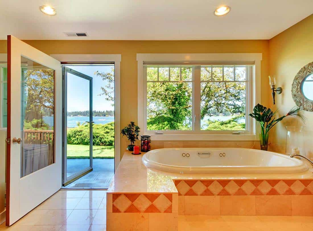 Large bathroom with tub and lake view window