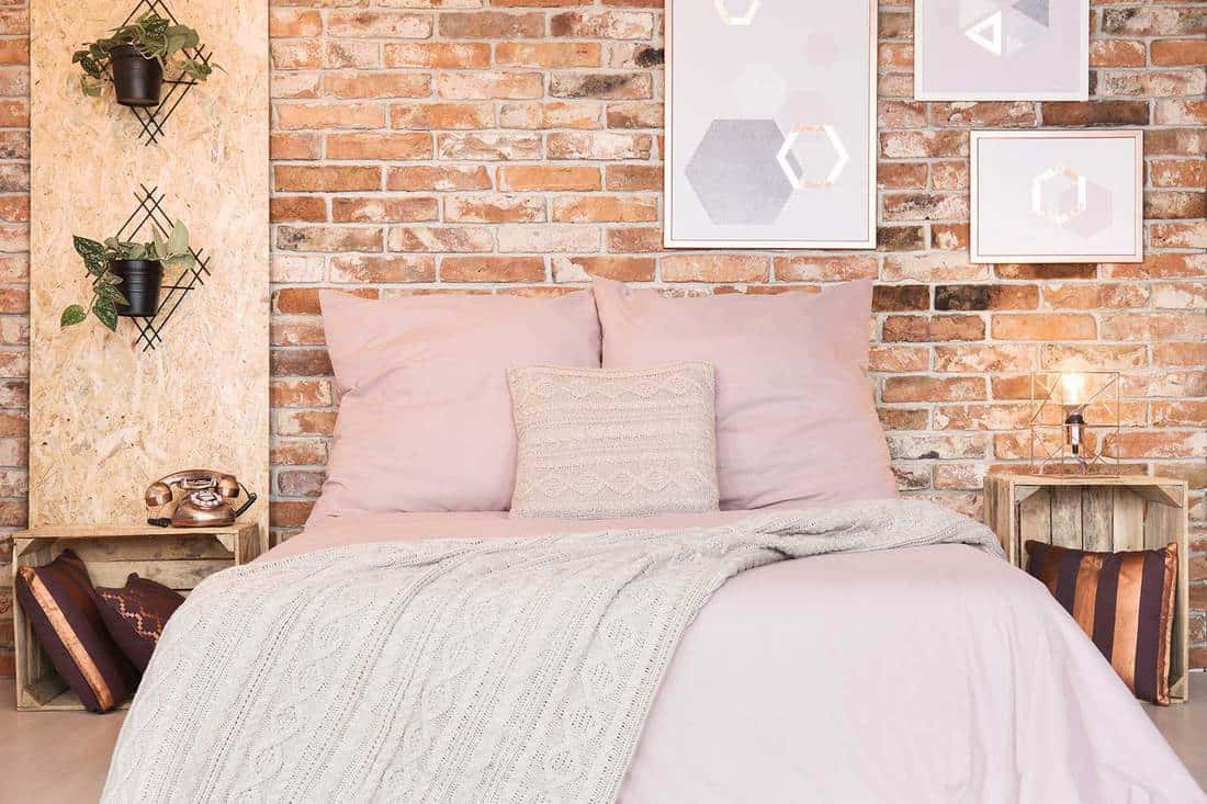 Loft bedroom with brick wall, double bed and pink bedding