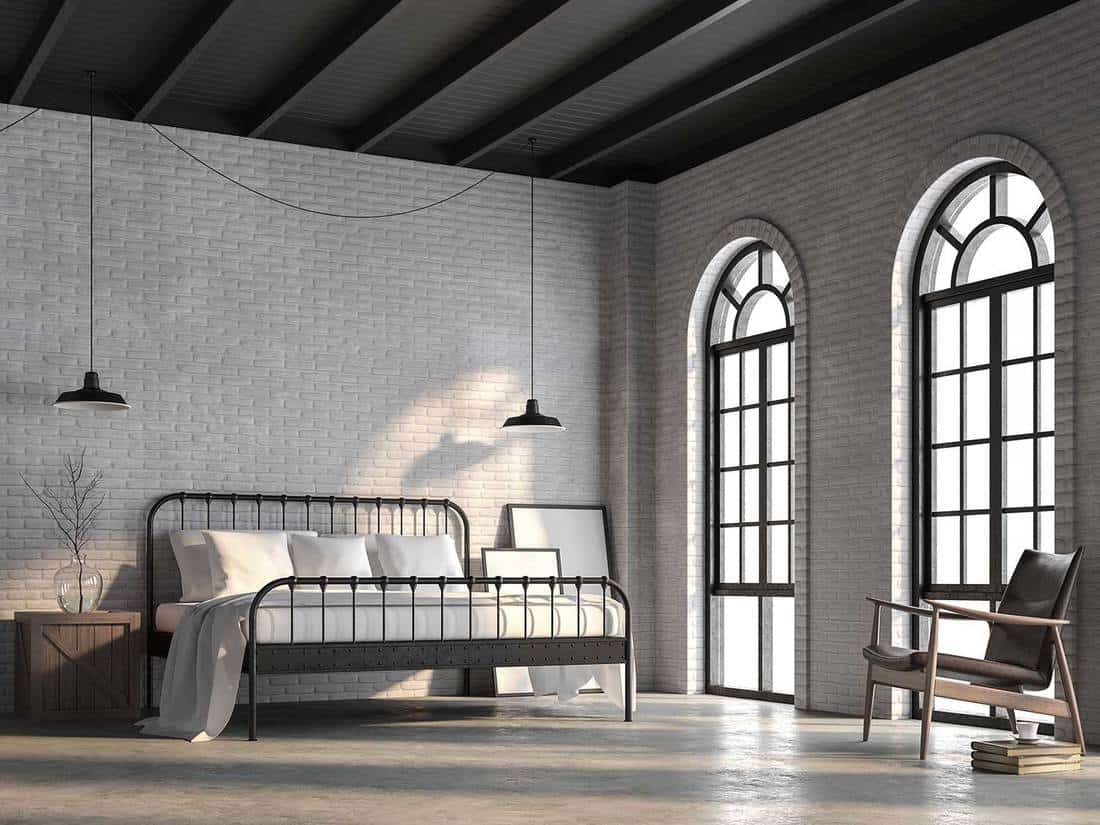 Loft bedroom with white brick wall, polished concrete floor and black wood ceiling