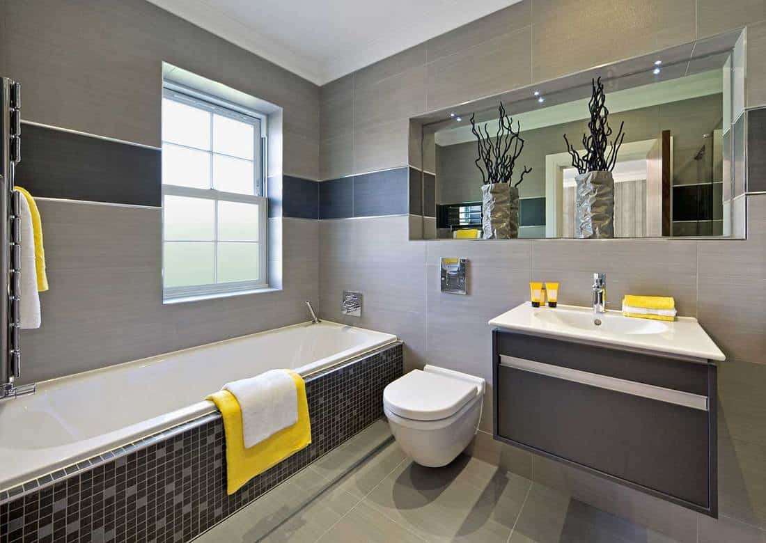 Luxury modern bathroom with white and yellow towels and wall mounted toilet