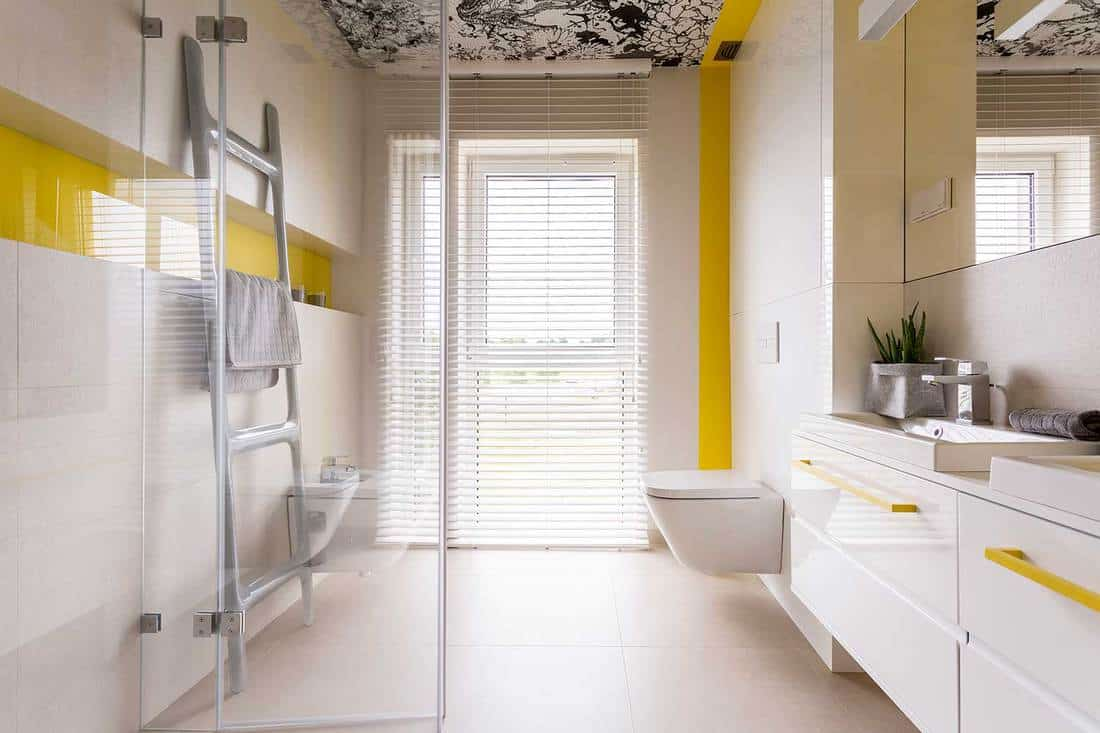 Luxury stylish bathroom with white cabinets, mirror, ladder tower rack, window, glass door and yellow details