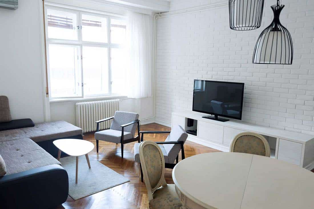 Minimalist living room with chairs table inside and white brick wall