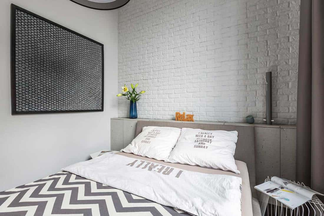 Modern bedroom with double bed and white brick wall