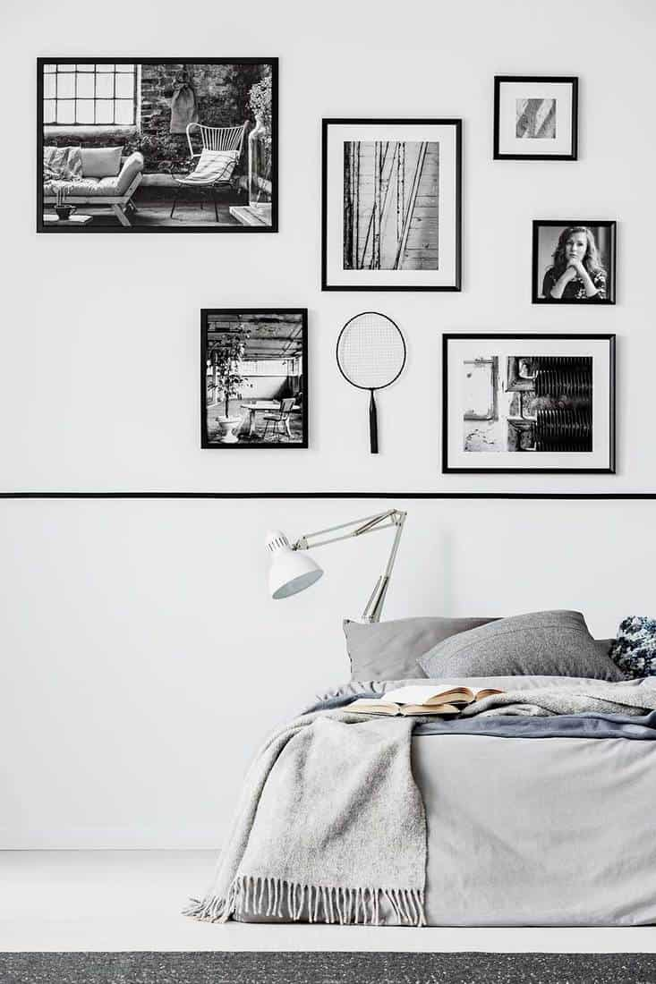 Modern bedroom with king size bed with grey bedding, white lamp and gallery of black and white poster