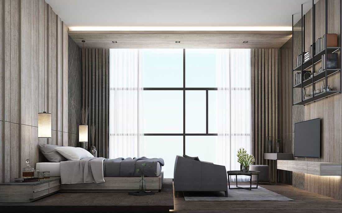 Modern luxury bedroom interior with wooden wall, flat screen tv, grey sofa and table