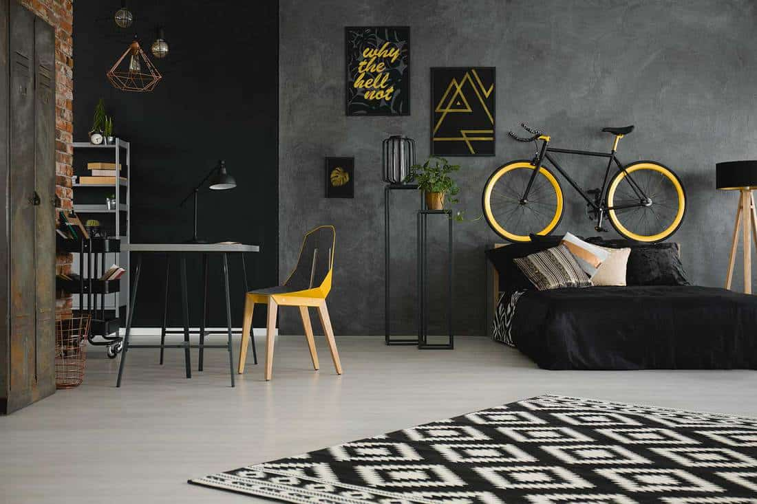 Patterned carpet in teenager's industrial bedroom interior with yellow chair, desk and bike above bed