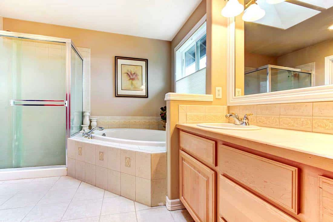 Refreshing bathroom with yellow and beige walls, tile floor, wood cabinets, glass shower and bath tub