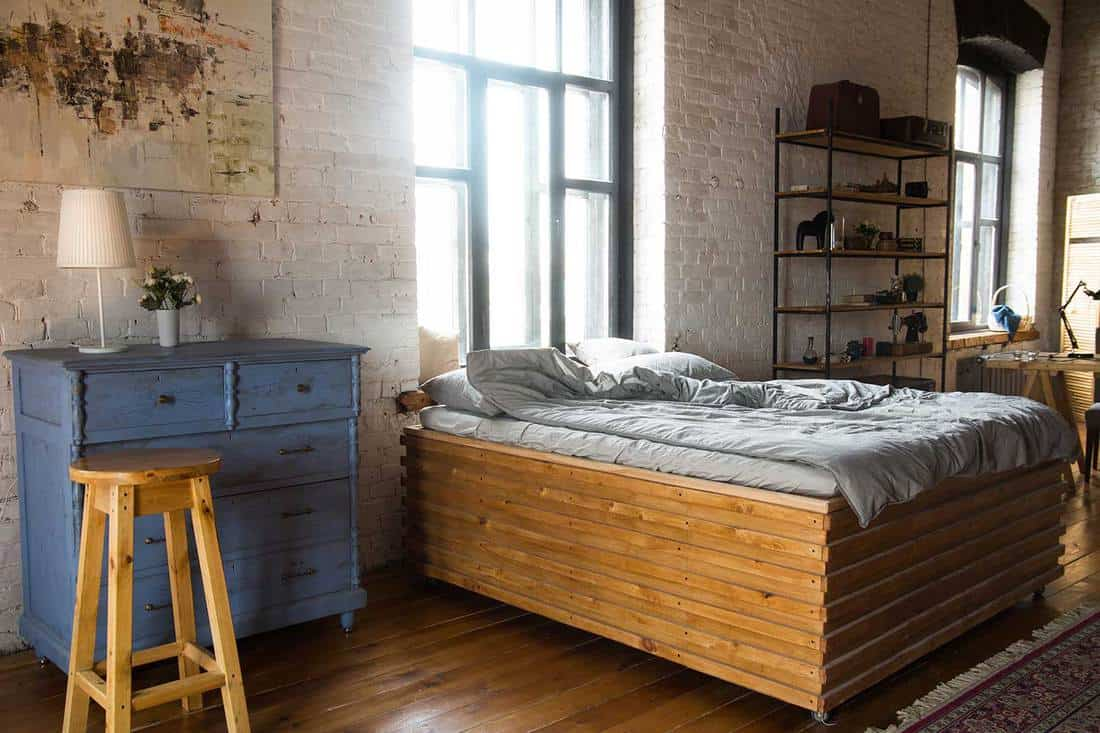 Retro industrial style bedroom with a large wooden bed, window and hardwood flooring