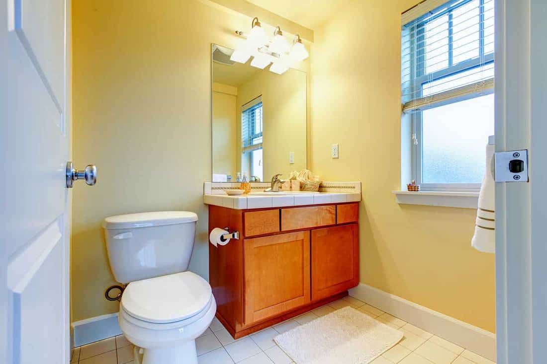 Small bathroom with window, yellow walls and white tile floor