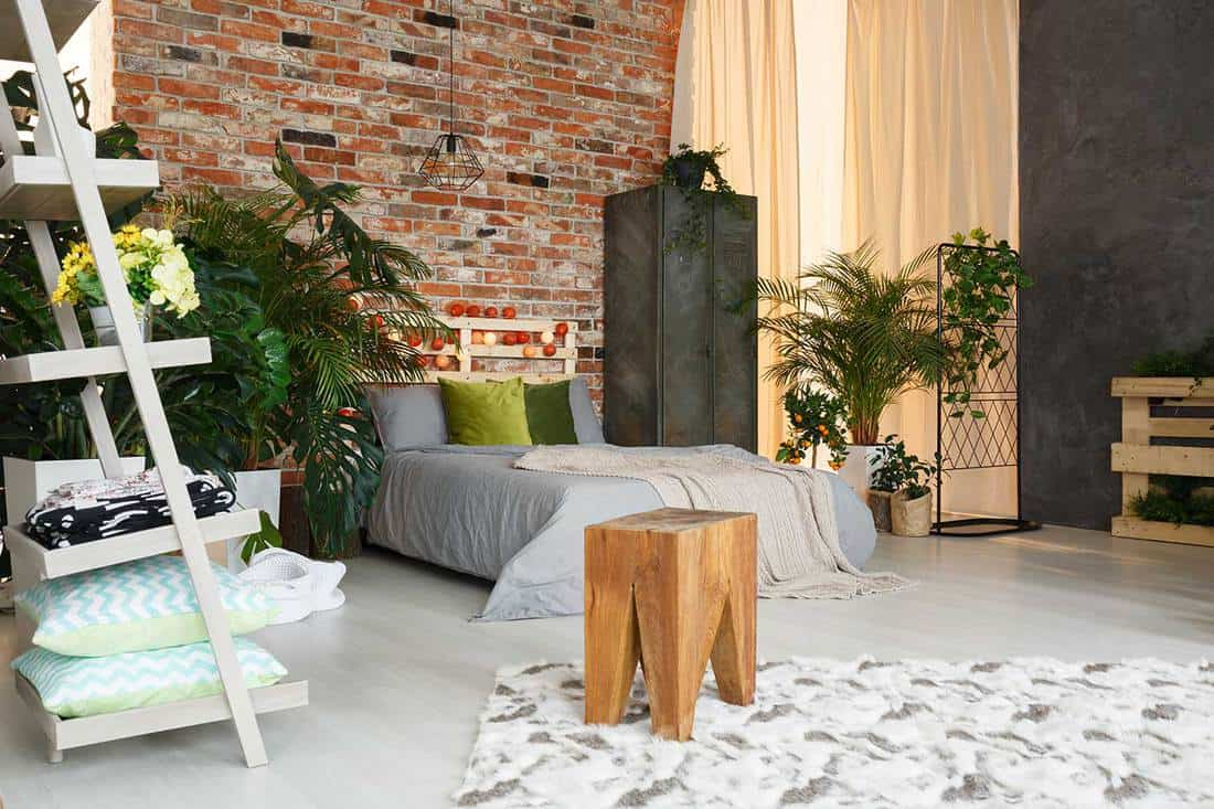 Spacious ecological bedroom with brick wall and industrial lighting