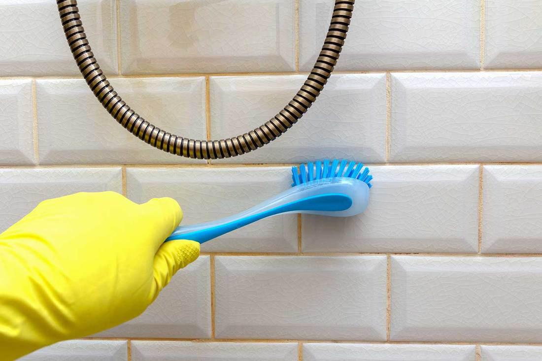 Tile cleaning in the bathroom with brush in hand in yellow glove