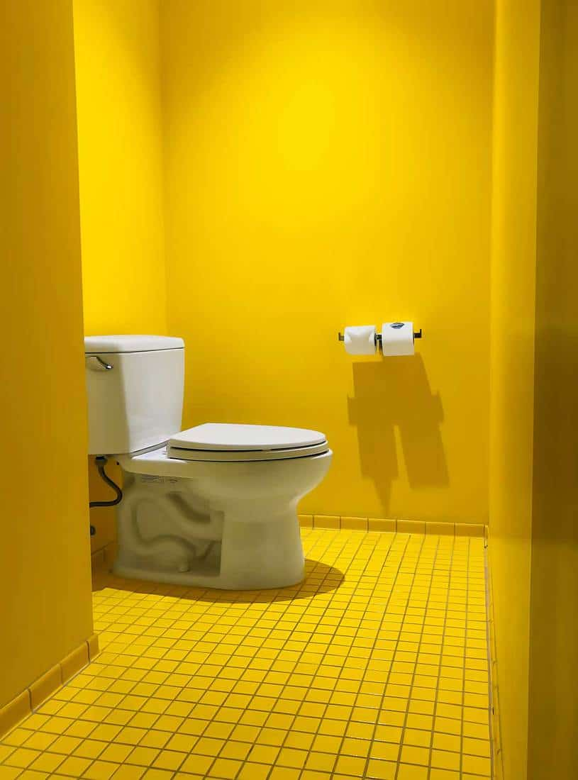 White toilet in yellow painted and tiled hotel bathroom