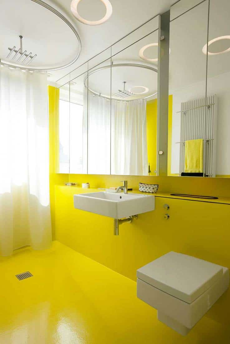 Yellow bathroom with ceiling mounted circular head-shower, big mirrors and wall mounted toilet