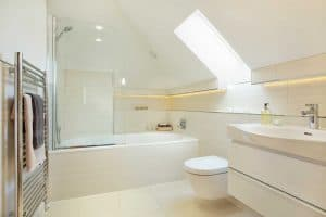 Attic bathroom with shower, toiletries, candles and towels in a luxury manor house